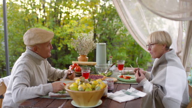 Retired Caucasian Couple Eating Simple Meal in Garden and Chatting
