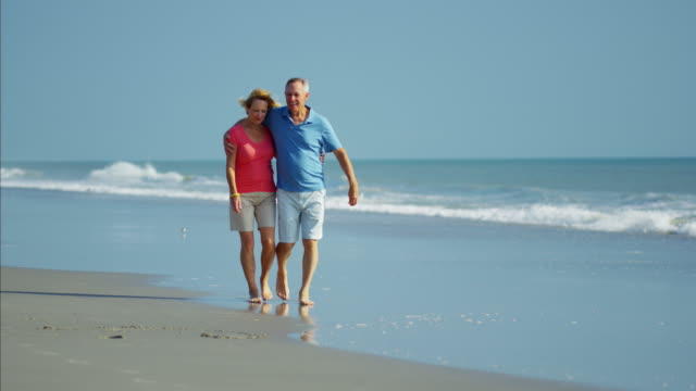 vídeos de stock e filmes b-roll de retired caucasian couple in colorful clothing on beach - medicare