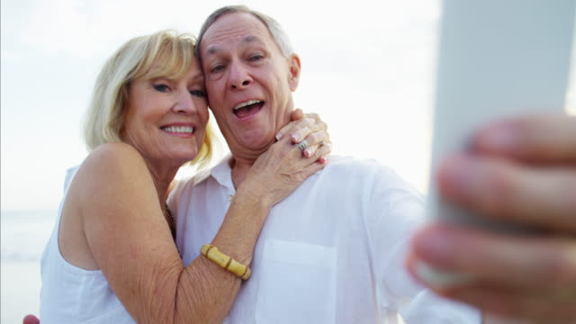 Retired Caucasian couple in white clothing taking selfie Happy retired Caucasian couple white clothing smartphone technology selfie leisure tourism travel Medicare beach RED DRAGON medicare stock videos & royalty-free footage