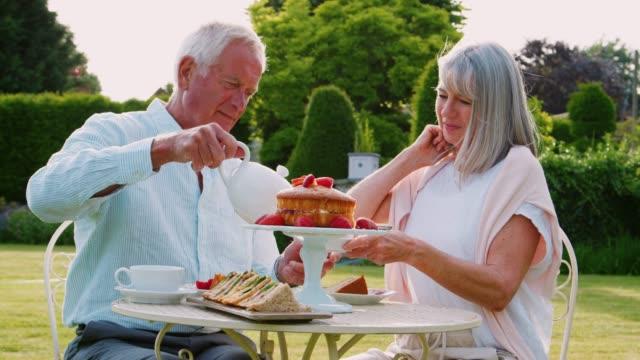自宅の庭でアフタヌーン ティーを楽しむ退職カップル - お茶の時間点の映像素材/bロール