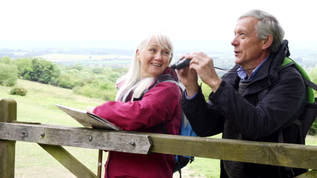 Retired Couple On Walking Holiday Looking Through Binoculars