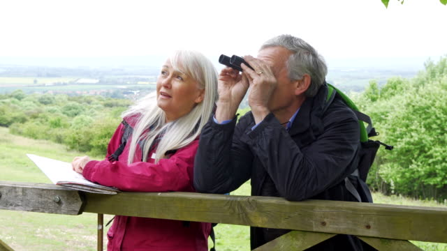 双眼鏡を見てウォーキングホリデーで引退したカップル - バードウォッチング点の映像素材/bロール