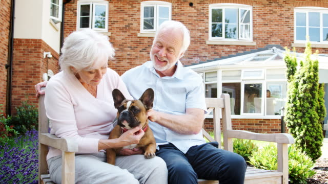 Retired Couple Sitting On Bench And With Pet French Bulldog In Assisted Living Facility
