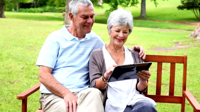 Retired couple sitting on park bench using tablet video
