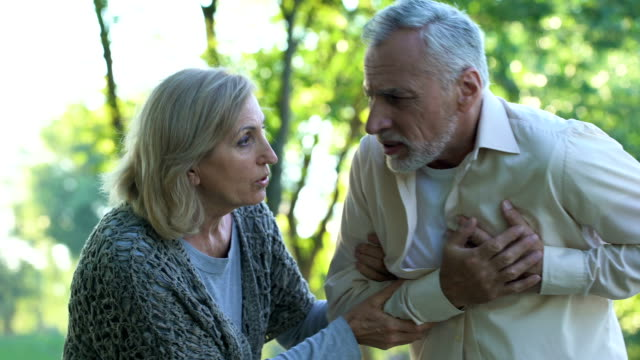 vídeos de stock e filmes b-roll de retired couple walking in park, male pensioner suffering from heart attack - enfarte