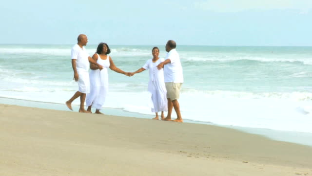 Jubilados pareja étnica caminar junto al mar - vídeo