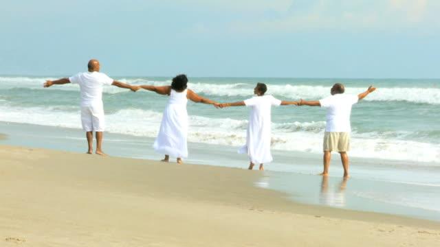 vídeos y material grabado en eventos de stock de jubilados pareja étnica caminar junto al mar - árboles genealógicos