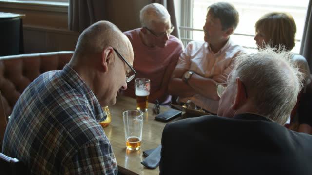 pensionerade vänner möte för drinkar och middag titta på menyer i puben - pub bildbanksvideor och videomaterial från bakom kulisserna
