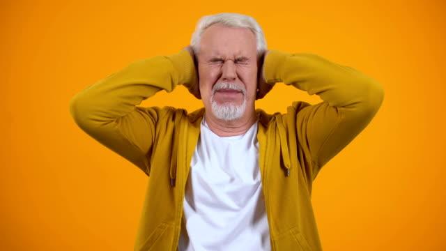 orecchie di copertura maschili in pensione da palme scontente di pettegolezzi su sfondo arancione - ear talking video stock e b–roll