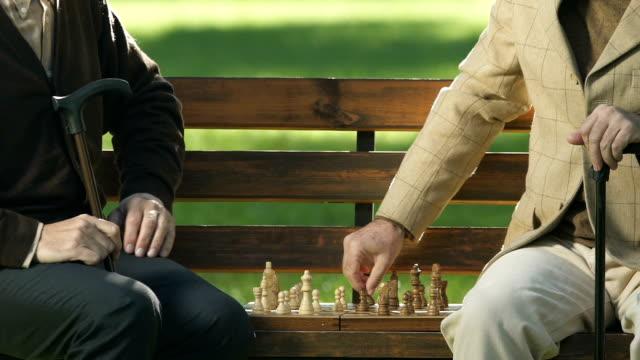 pensionierte männliche freunden schach auf bank, spaß zusammen, schachmatt - könig schachfigur stock-videos und b-roll-filmmaterial
