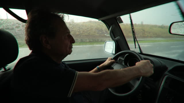 Retired man holding steering wheel driving on highway road during rainy afternoon. Older man driving on a trip traveling on a wet road in 4K video