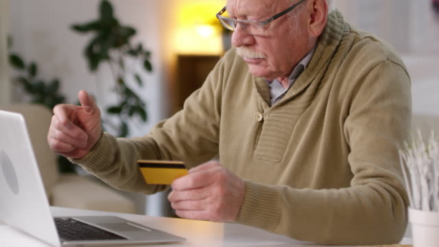 retired man learning to shop online - credit card стоковые видео и кадры b-roll