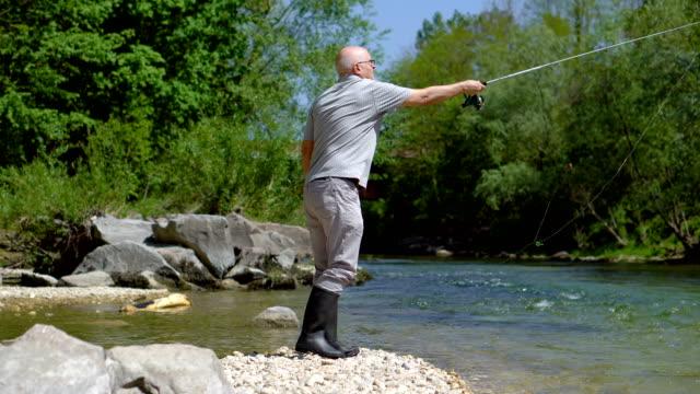 retired man throwing angler of fishing rod into river - spranga video stock e b–roll