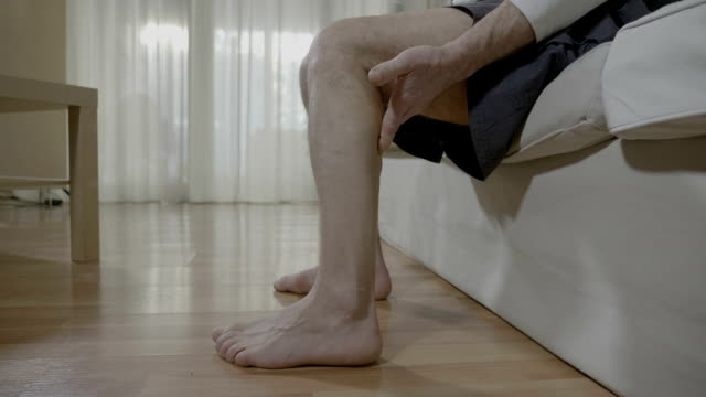 Retired man with muscular cramp sitting in bedroom rubbing his leg healing the unpleasant strain video