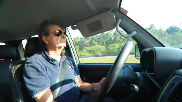 Retired older man driving casually on highway road traveling going on a road trip video
