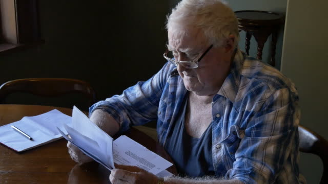 retired pensioner at table stressed looking at debt - foreclosure stock videos & royalty-free footage