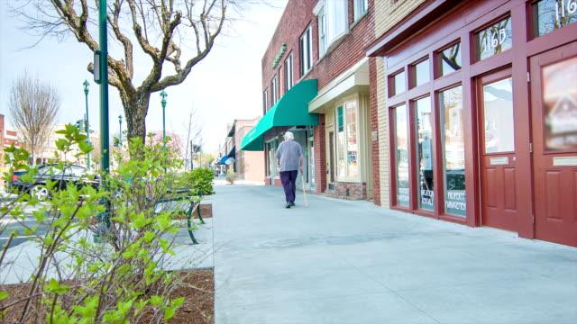 vídeos y material grabado en eventos de stock de jubilados ciudadano senior caminando por la calle main street de estados unidos - calle principal calle