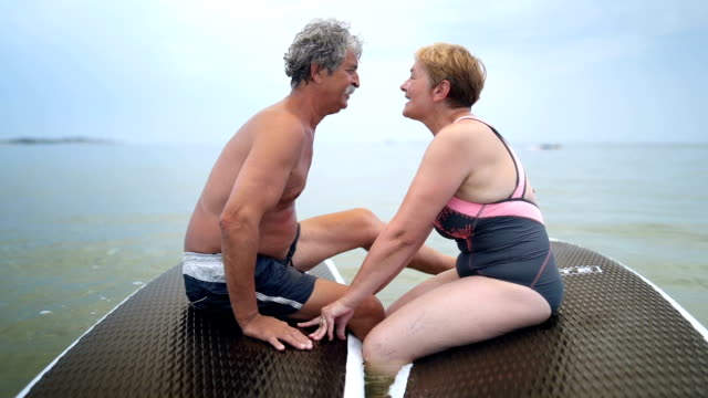 Retired senior couple enjoying on the sea Senior couple is sitting on the paddle board, talking and kissing. Montage. kissing stock videos & royalty-free footage