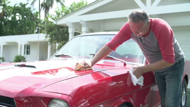 Retired Senior Man Cleaning Restored Classic Car