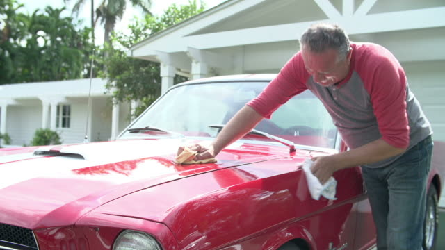 Retired Senior Man Cleaning Restored Classic Car Senior man polishing bonnet of restored classic car.Shot on Sony FS700 at frame rate of 25fps sports car stock videos & royalty-free footage