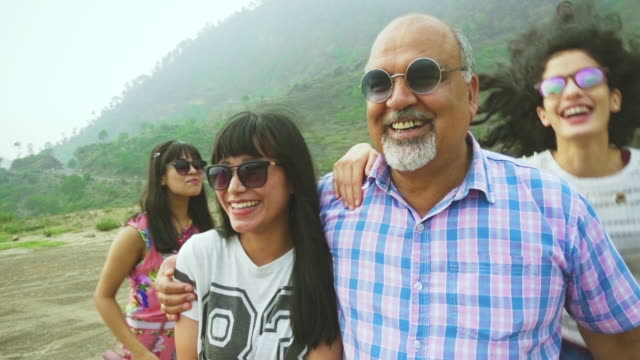 Retired senior man with daughter and her friends enjoy outing. Slow motion video of Asian/Indian, senior, a retired man enjoys an outing with their young adult daughter and her friends in the mountains of Himachal Pradesh at day time. indian family stock videos & royalty-free footage