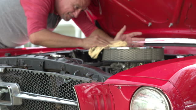 Retired Senior Man Working On Restored Car In Slow Motion Camera tracks upwards in slow motion showing senior man working under bonnet of restored classic car.Shot on Sony FS700 at frame rate of 50fps sports car stock videos & royalty-free footage