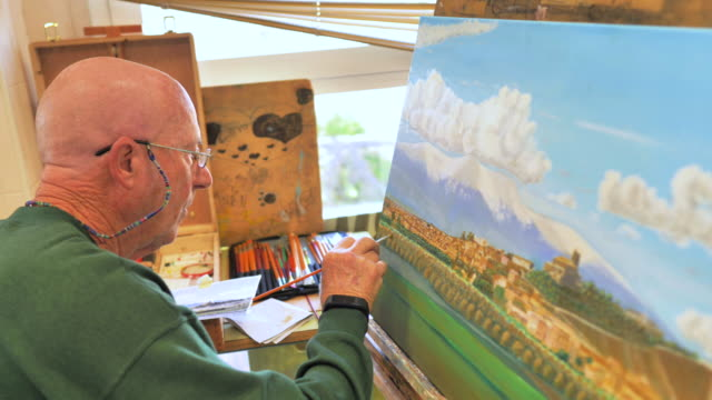 retired student on painting course painting in oil