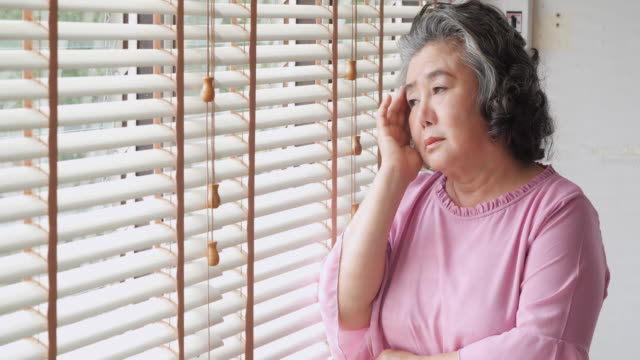 vídeos de stock e filmes b-roll de retired woman alone in home.sad old woman standing alone near a window and thinking about something: sadness and depression in a natural lighting footage - alzheimer