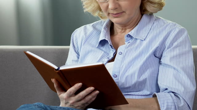 Retired woman sitting on couch and reading book, avid book reader, leisure time video