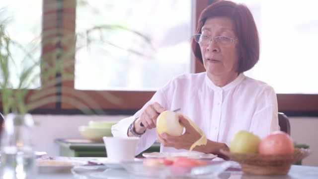 retired woman slices apple in home kitchen