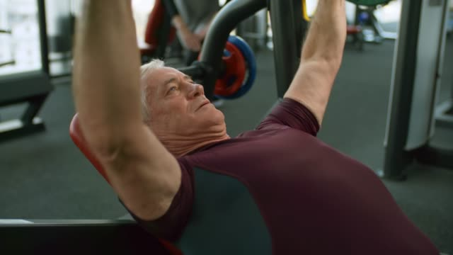 vídeos y material grabado en eventos de stock de jubilados haciendo press de banca - entrenamiento con pesas