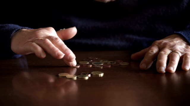 Retiree old woman's hand counting coins on the table,close up Retiree old woman's hand counting coins on the table,close up poverty stock videos & royalty-free footage