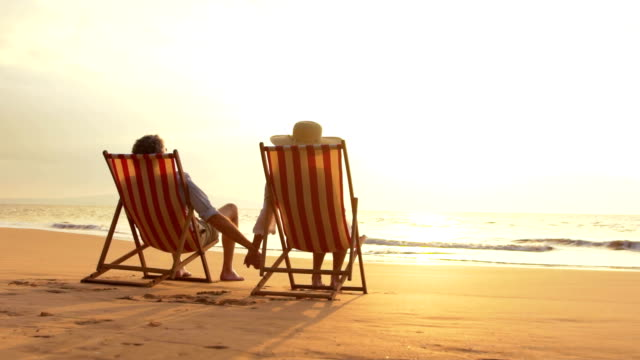 Retirement Vacation Concept, Happy Mature Retired Couple Enjoying Beautiful Sunset at the Beach video