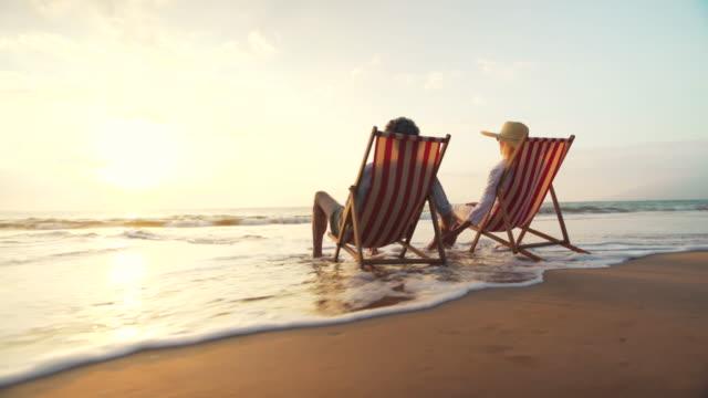 Aposentadoria conceito de férias, aposentado casal maduro feliz aproveitando o belo pôr do sol na praia - vídeo