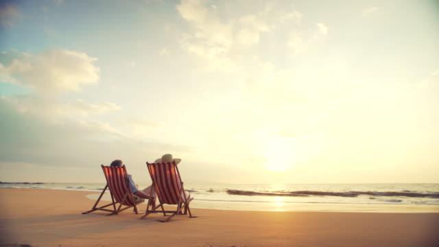 vídeos y material grabado en eventos de stock de concepto de jubilación vacaciones, jubilados de una pareja madura feliz disfrutar de hermosa puesta de sol en la playa - cómodo conceptos