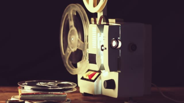 retro 8mm movie projector working in the dark room. dolly shot