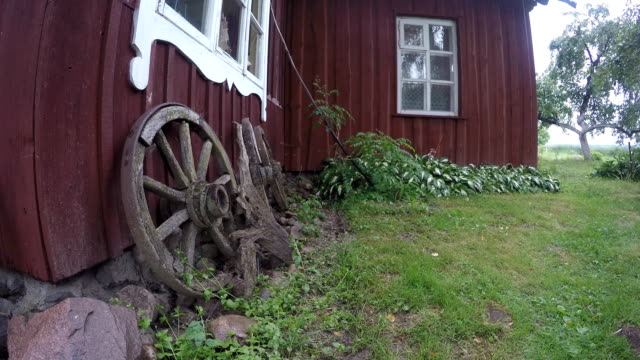 Retro cart wheels near wooden house and rain drops splash from roof video