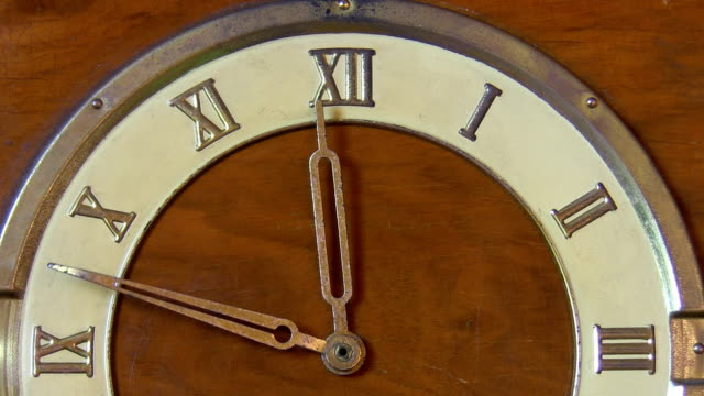 Retro clock with Roman numerals Close up view of a half face of antique wooden clock with Roman numerals showing time approaching 12 midday or midnight symbolising symbolizing end of an old year and new year coming. midday stock videos & royalty-free footage