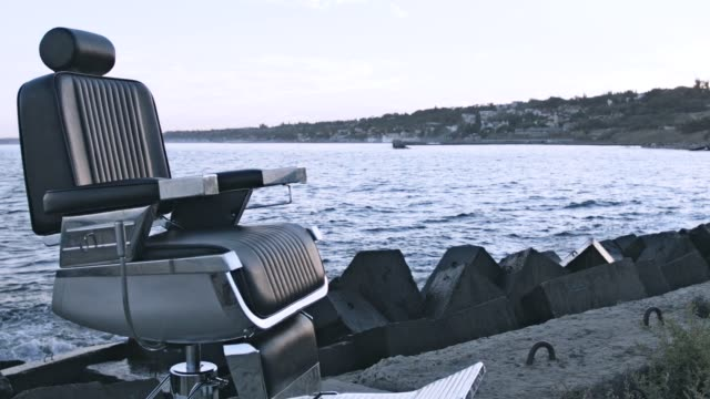 Retro hairdresser chair standing on evening sea shore. Hairdressing on beach video