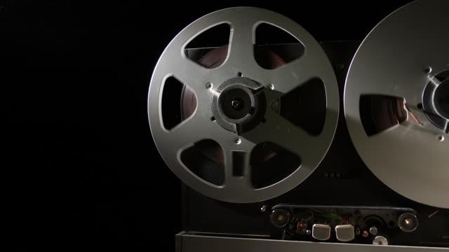 registratore analogico da bobina a bobina da quarto di pollice retrò gestito in una stanza buia - bobina apparecchiatura di registrazione del suono video stock e b–roll