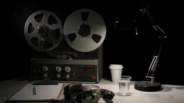retro quarter inch analog reel-to-reel recorder being operated in a darkened room - bobina apparecchiatura di registrazione del suono video stock e b–roll