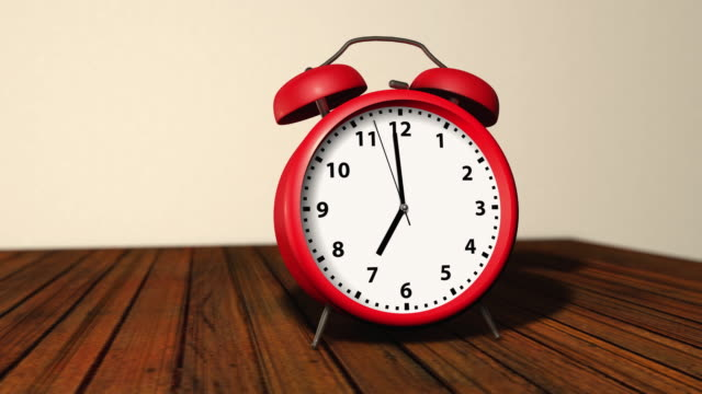 Retro red alarm clock with two bells on top, ringing at 7 o`clock