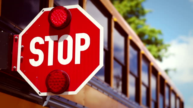 Retro school bus color graded shot of stop light flashing video