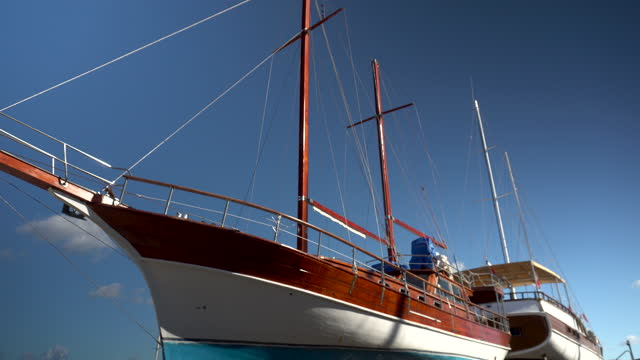 Retro ship under restoration. A wooden colorful ship stands on land. Repair of the ship. Bay