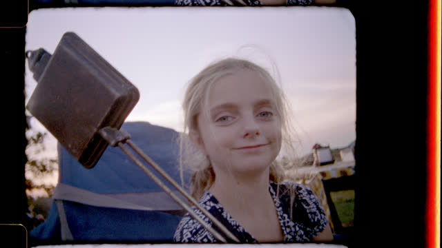 Retro style film footage of girl smiling and laughing at camera while sitting by campfire with vintage sandwich toaster.