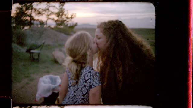Retro style film footage of mother and daughter sharing a sweet kiss at picnic table and daughter turning to kiss camera on family camping trip.