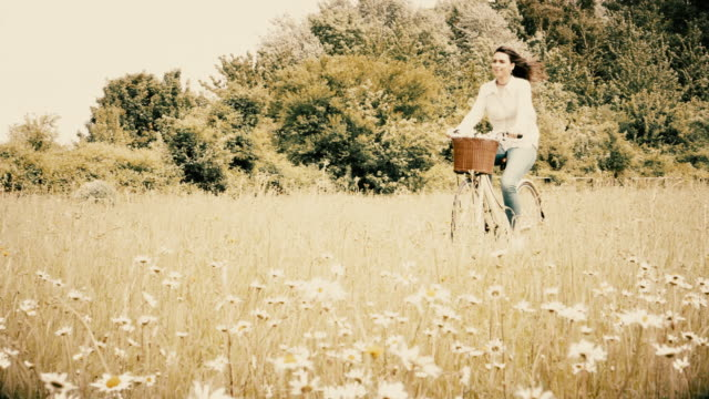 Retro style, young woman cycling through a meadow, riding a retro bicycle.