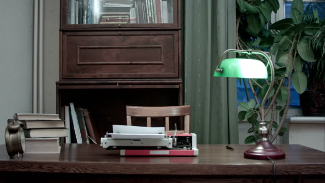 Retro typewriter with books and green lamp on the table Retro typewriter with books and green lamp on the table. Lamp turns on and off. Professional shot on BMCC RAW with high dynamic range. You can use it e.g. in your commercial video, business, presentation, broadcast video. lamp shade stock videos & royalty-free footage
