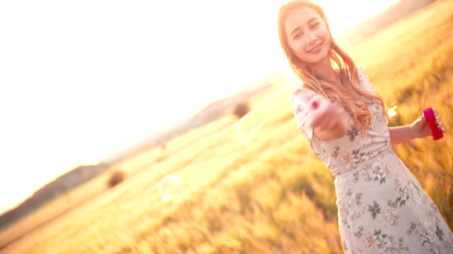 Retro woman blowing bubbles in field of barley at sunset