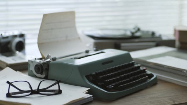 Retro writer desk with typewriter Old fashioned writer and reporter desk with typewriter, vintage camera and record player: creativity and retro revival concept typewriter stock videos & royalty-free footage